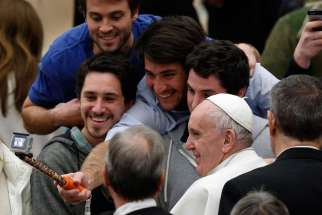 Young men take a selfie with Pope Francis as he leaves his general audience in Paul VI hall at the Vatican Jan. 20.