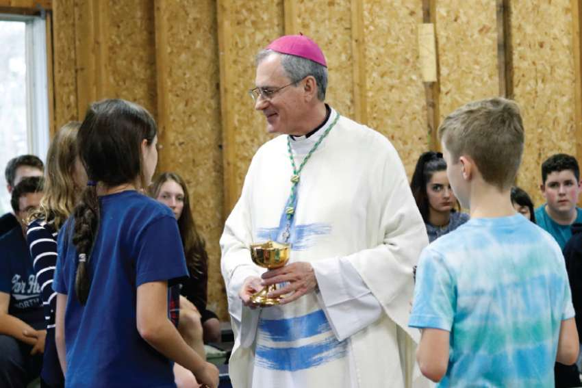 Bishop Ronald P. Fabbro talks with young people during CCLC week, a summer camp run by the London diocese.