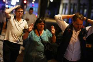 After a terrorist attack near the London Bridge June 3. people leave the area with their hands up. Seven people were killed and dozens injured when three terrorists in a van mowed down pedestrians on the bridge before stabbing a police officer and revelers around Borough Market.
