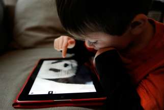 A boy uses the World Wildlife Fund app to take a closer look at pandas on an iPad in early March. The American Academy of Pediatrics issued a new policy statement Oct. 28 on the dangers of too much screen time for children.