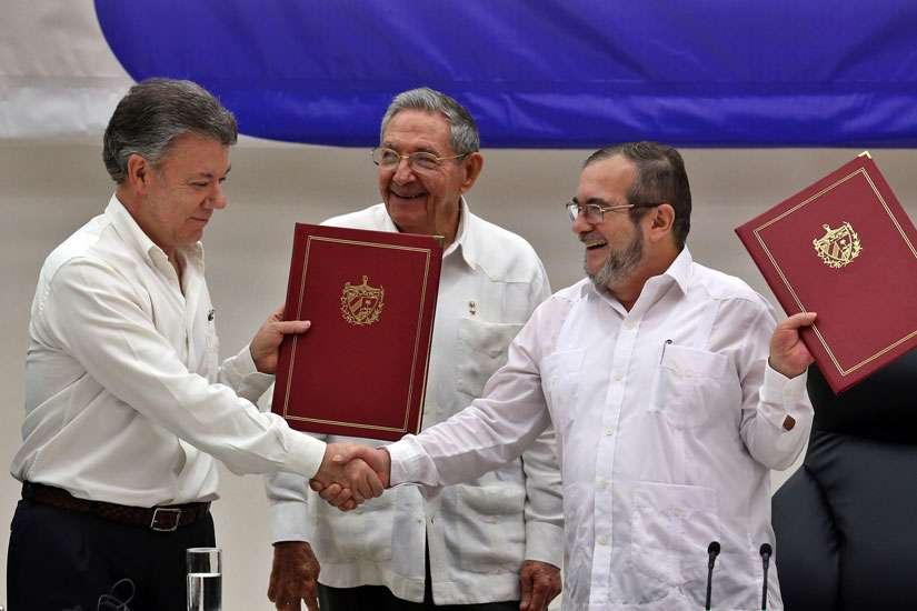 Colombian President Juan Manuel, left, shakes hands with FARC delegate Londono Echeverri 'Timochenko' in Havana Juen 23 as Cuban President Raul Castro looks on. The Colombian government and rebel group signed a bilateral ceasefire agreement in Cuba.