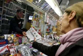 A woman buys a copy of Italian newspaper La Repubblica in Rome October 22, 2009.