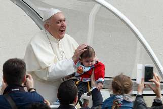 Pope Francis smiles as a papal security guard holds up a baby during his general audience in St. Peter's Square at the Vatican April 18.