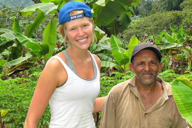 An Intercordia student and her host father on the cunuco or plantation in the Dominican Republic.