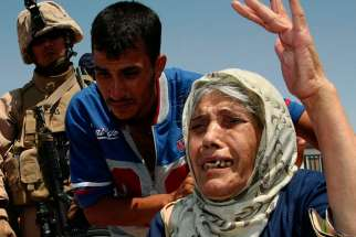 An elderly Iraqi woman fleeing violence gestures at the Al Waleed refugee camp in Iraq Aug. 19. One group of sick, elderly Iraqi Christians said they defied terrorist demands to convert to Islam or be killed.