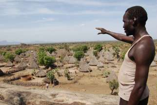 A man points at a village in rural South Sudan before the civil war. Most of the villages have been destroyed in the war.
