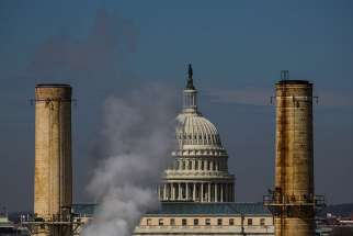 The dome of the U.S. Capitol is seen behind the smokestacks of the only coal-burning power plant in Washington in this March 10, 2014, file photo.