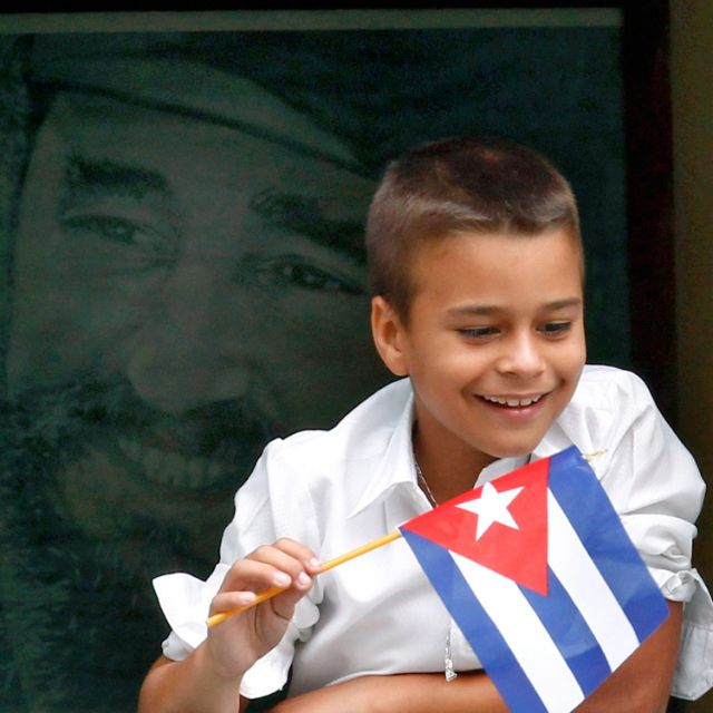 A boy holds a Cuban flag with a portrait of Fidel Castro behind him as he watches Pope Benedict XVI's caravan make its way to the airport in Havana March 28.