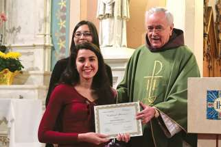 Sabrina Quartarone accepts her third-place certificate from Fr. Damian MacPherson during a presentation Mass Feb. 5 at St. Cecilia's Church.