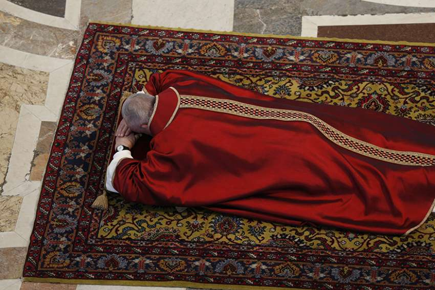 Pope Francis lies prostrate in prayer during the Good Friday service in St. Peter's Basilica at the Vatican April 19, 2019.