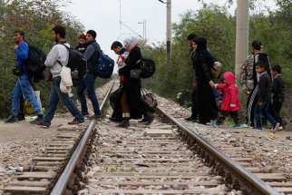 Refugees cross train tracks into Macedonia after arriving at a transit camp in Idomeni, Greece, Oct. 19. Thousands of refugees are arriving into Greece from Syria, Afghanistan, Iraq and other countries and then traveling further into Europe.