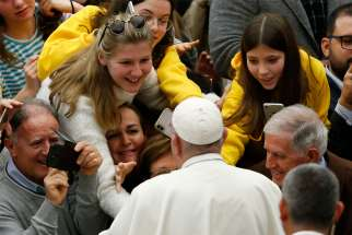 People greet Pope Francis as he leaves his general audience in Paul VI hall at the Vatican Dec. 18, 2019.