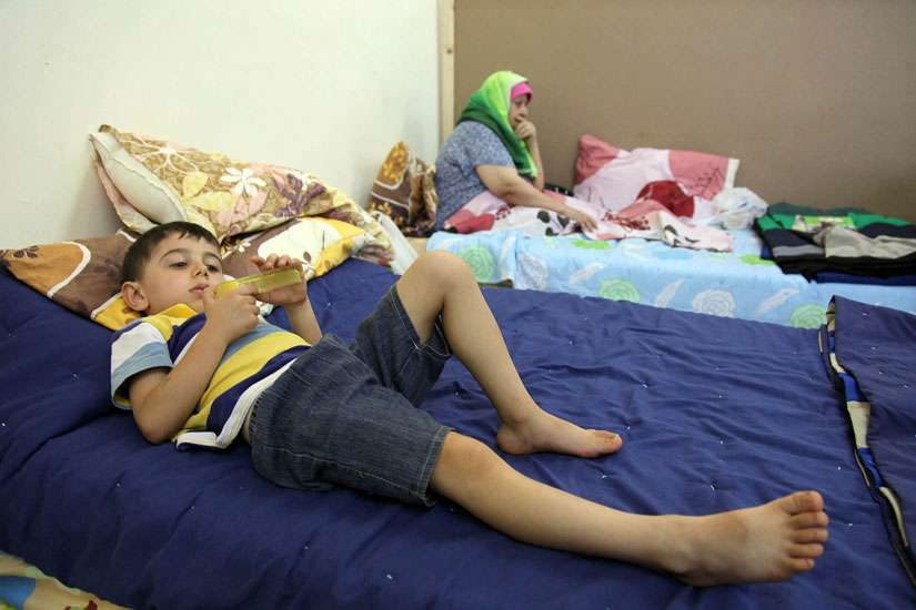 An Iraqi Christian child who fled from violence in Mosul, Iraq, lies on a bed in late August at a church in Amman, Jordan. A Catholic official warned that funding will soon run out for the refugees, who fled Islamic State militants.