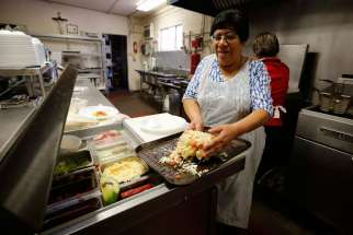 Cook Amelia Patrykus assembles tacos in the kitchen of La Tilma Mexican Grill in mid-February at Sacred Heart Church in El Paso, Texas. The eatery serves up generous plates of homestyle food at value prices.