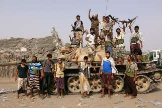 Tribal fighters loyal to the Yemeni government pose for a photo by a tank near Hodeida, Yemen, June 1.