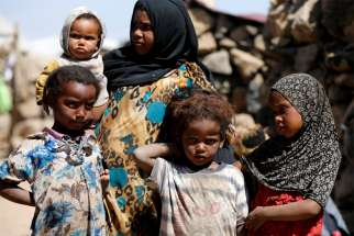 A woman stands with children at a makeshift camp for internally displaced people near Sanaa, Yemen, Jan. 28, 2019. The United Nations says one child dies every 10 minutes in Yemen.