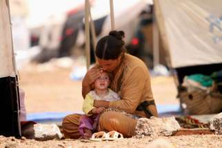 "A woman who fled the violence in the Iraqi town of Sinjar sits with a child inside a tent at a camp in Syria's northern town of Qamishli Aug. 17. Returning from a visit to the Kurdish region of Iraq, Syriac Catholic Patriarch Ignace Joseph III Younan cal led the Islamic State invasion ""pure and simple religious cleansing and attempted genocide."""