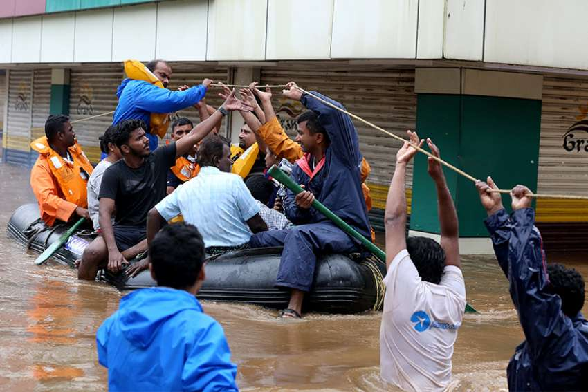 Rescue workers evacuate people from flooded areas Aug. 16 after the opening of a dam following heavy rains on the outskirts of Cochin, India. The Catholic Church has joined relief efforts as unprecedented floods and landslides continue to wreak havoc in India's Kerala state, killing at least 75 people within a week.