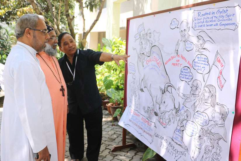 Bishop Stephen Rotluanga of Aizawl, India, explains his cartoon on the conference to Cardinal Baselios Cleemis Thottunkal in Bangalore March 9.