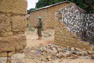 A Bangladeshi United Nations peacekeeping soldier stands amid homes destroyed by violence in 2017 in the abandoned village of Yade, Central African Republic. Bishops in the Central African Republic have declared two days of mourning for victims of recent massacres.