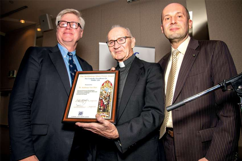 Catholic Civil Rights League president Phil Horgan, left, presents Fr. Tony Van Hee with the Exner Award, accompanied by CCRL executive director Christian Elia.