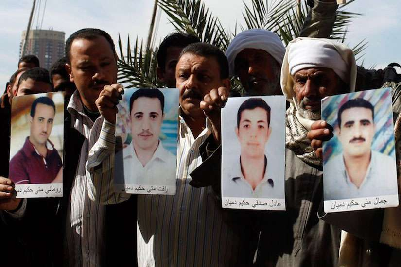 Families of the 27 Egyptian Coptic Christians workers kidnapped in the Libyan city of Sirte, hold pictures of their kidnapped relatives in front of the U.N. office in Cairo January 19, 2015.