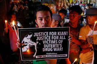 A young man in Manila, Philippines, holds a placard Aug. 25 at a memorial for Kian Delos Santos, a 17-year-old shot in an escalation of Philippine President Rodrigo Duterte's war on drugs.