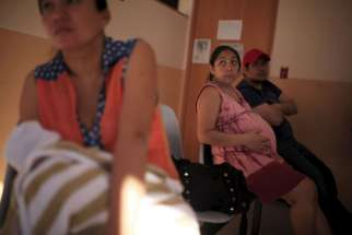 A pregnant woman waits to be seen Jan. 29 at the Women's National Hospital in San Salvador, El Salvador. The growing number of Zika virus cases in the U.S. has inflamed the abortion debate.
