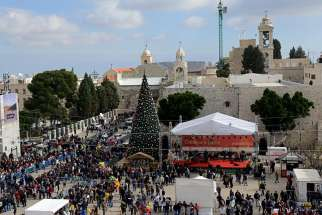 People gather in Manger Square and the Church of Nativity on Christmas Eve in Bethlehem, West Bank.
