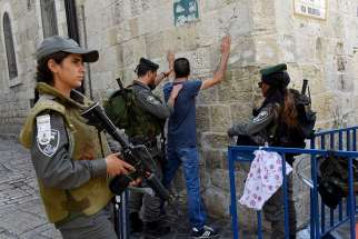 Israeli border police make a Palestinian face the wall for a body security check on the Via Dolorosa in Jerusalem's Old City Oct. 18, 2015. Following a mid-July shooting deaths of two Israeli policemen and three gunmen, tension has been running high in the Old City.