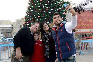 Fadi Hazboun, 20, takes a selfie of with his Catholic family from Nazareth in front of the Christmas tree in Manger Square outside the Church of Nativity in Bethlehem, West Bank, Dec. 21. Pictured with him are his father, Afif, mother, Nardin, and his 8- year-old brother, Jowan.