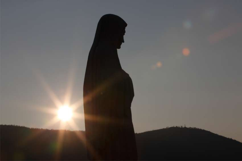 The sun sets behind a statue of Mary on Apparition Hill in Medjugorje, Bosnia-Herzegovina, in this Feb. 26, 2011, file photo. Senior Vatican representatives joined dozens of bishops and hundreds of priests at the first officially approved church youth festival at the site Aug. 2-6, 2019, three months after Catholic pilgrimages were authorized by the pope.
