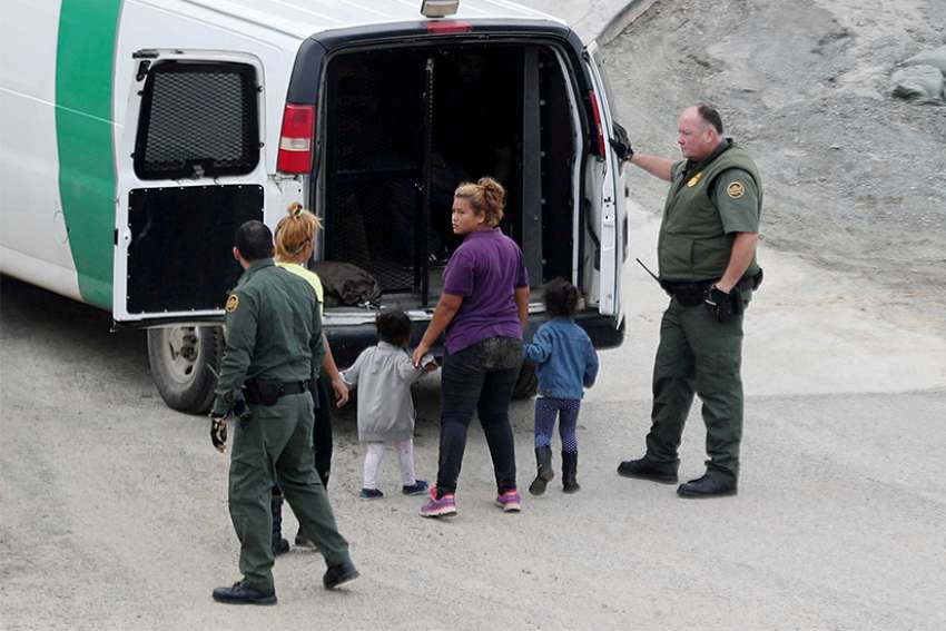 U.S. Customs and Border Protection officials Dec. 9 detain a migrant woman and children after they crossed illegally with other migrants in the U.S. from Mexico at International Friendship Park in San Diego. They were part of a caravan of thousands from Central America trying to reach the United States.