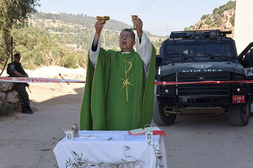 Fr. Aktham Hijazin of Beit Jalla, West Bank, celebrates Mass Sept. 3 in front of Israeli border police. Israel is uprooting the trees to make the way for the controversial separation barrier in the Cremisan Valley.