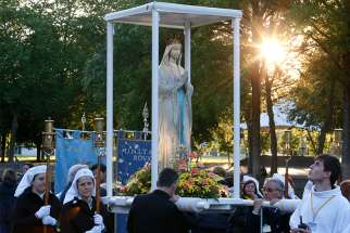 "Attendants prepare to carry a statue of Mary in procession at the Shrine of Our Lady of Lourdes in southwestern France May 16, 2014. In Nov. 29 remarks, Pope Francis encouraged rectors and workers at shrines to make guests feel ""at home."""