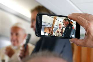 Pope Francis is pictured on a cell phone video with Vatican spokesman, Greg Burke, as he greets journalists aboard his flight from Rome to Vilnius, Lithuania, Sept. 22.