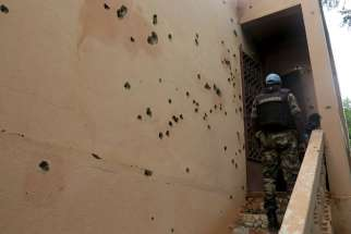 An armed police officer climbs stairs at the hotel where 17 people died in Sevare, Mali, Aug. 11.