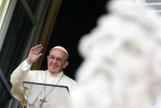 Pope Francis waves to the crowd as he leads the Angelus from the window of his studio overlooking St. Peter's Square Oct. 29 at the Vatican.