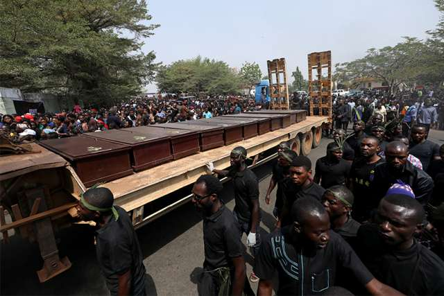 Men march along a truck Jan. 11 carrying the coffins of people killed by Fulani herdsmen in Makurdi, Nigeria. With at least 80 people killed since the start of the year in conflict over fertile land in Nigeria, the nation's bishops condemned what they call brutal massacres of innocent people.