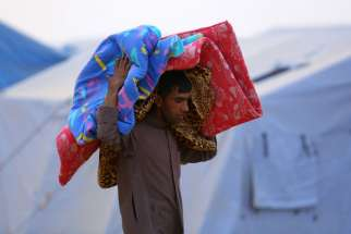 An Iraqi refugee carries a mattress at a camp near the northern city of Irbil June 12. Hundreds of thousands of people who have fled their homes in Mosul are left without access to aid, officials said