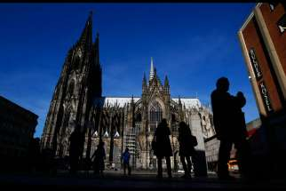 People are silhouetted against the Cologne Cathedral in Germany Jan. 25. Catholic bishops in Germany and Austria urged their countries to continue accepting refugees, despite demands for new restrictions after New Year's Eve violence in Cologne and other cities.