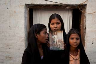 The daughters of Asia Bibi, a Catholic eventually aquitted of blasphemy, pose in 2010 with an image of their mother while standing outside their residence in Sheikhupura, Pakistan. Bibi, the Pakistani Catholic mother freed after eight years on death row, says people must help Pakistanis falsely implicated in blasphemy cases get released.