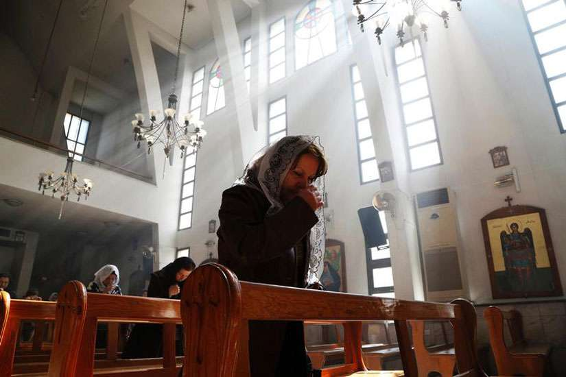 An Assyrian woman prays at a church in Damascus March 1 during a special Mass for Assyrian Christians abducted by Islamic State fighters. In early August, Islamic State militants attacked Qaryatain, a town where Christians sought refuge after leaving Aleppo, and Hawwarin, a nearby Assyrian village, where 2,000 Assyrian Christians were forced to flee.