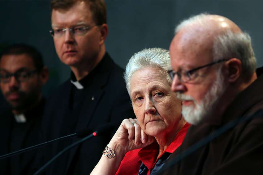 "Marie Collins, center, then member of the Pontifical Commission for the Protection of Minors, watches as Cardinal Sean P. O'Malley of Boston, president of the commission, speaks during a briefing at the Vatican May 3, 2014. Collins, who left the commission, told the Irish Times that Pope Francis ""should admit responsibility the Vatican and church leadership hold for past events in Ireland."" Also pictured is Jesuit Father Hans Zollner, a professor of psychology and president of the Center for Child Protection at the Pontifical Gregorian University in Rome."