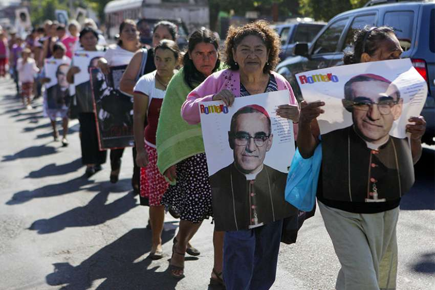 People hold posters showing the image of St. Oscar Romero during a 2014 protest in San Salvador, El Salvador. The protest was against the decision of the mayor to name a street after deceased Army Maj. Roberto D'Aubuisson, allegedly the mastermind of the 1980 killing of St. Romero.