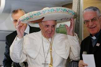 Pope Francis tries on a sombrero while meeting journalists aboard his flight to Havana Feb. 12. Traveling to Mexico for a six-day visit, the pope is stopping briefly in Cuba to meet with Russian Orthodox Patriarch Kirill of Moscow at the Havana airport.