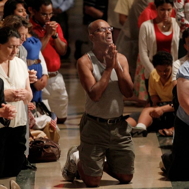"A man prays amid the overflow crowd during Mass at the Basilica of the National Shrine of the Immaculate Conception in Washington July 4, the final day of the bishops' ""fortnight for freedom"" campaign. The observance, which began with a June 21 Mass in B altimore, was a two-week period of prayer, education and action on preserving religious freedom in the U.S."
