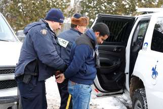 A man who told police he was from Mauritania is taken into custody Feb. 14 by Royal Canadian Mounted Police officers after walking across the U.S.-Canada border into Quebec.