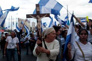 A demonstrator holds a crucifix during a protest against Nicaraguan President Daniel Ortega's government in Managua, Nicaragua, May 15.
