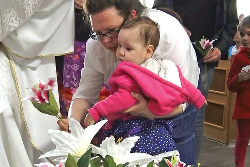 Lily Hunter, with her daughter Kateri, who was named in honour of the Indigenous saint, lays flowers in the Cathedral in St. Paul. St. Kateri was canonized in 2012.